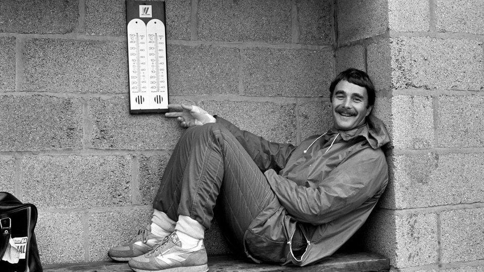 Nigel Mansell sheltering from the rain at Silverstone in 1985