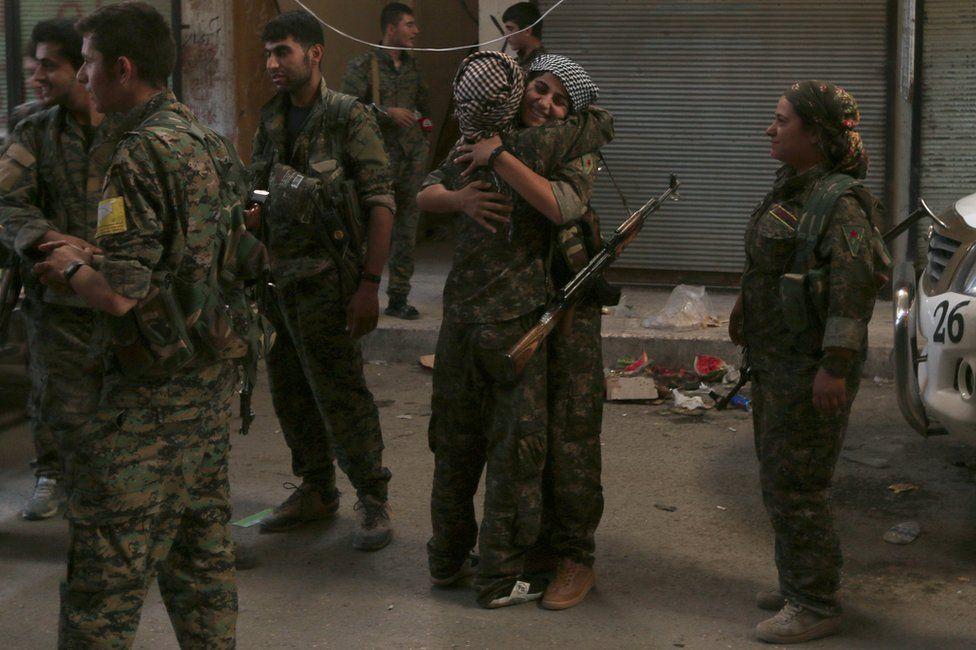 SDF fighters celebrate inside Manbij, Syria, 10 August