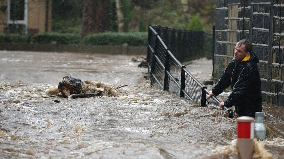 Residents battle against floodwater as the River Calder bursts its banks in the West Yorkshire town of Mytholmroyd on 26 December 2015