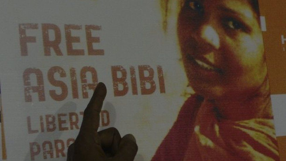 In this photograph taken on September 27, 2016, Ashiq Masih, husband of Asia Bibi, a Christian woman facing death sentence for blasphemy, points to a poster bearing an image of his wife Asia at a living area in Lahore.