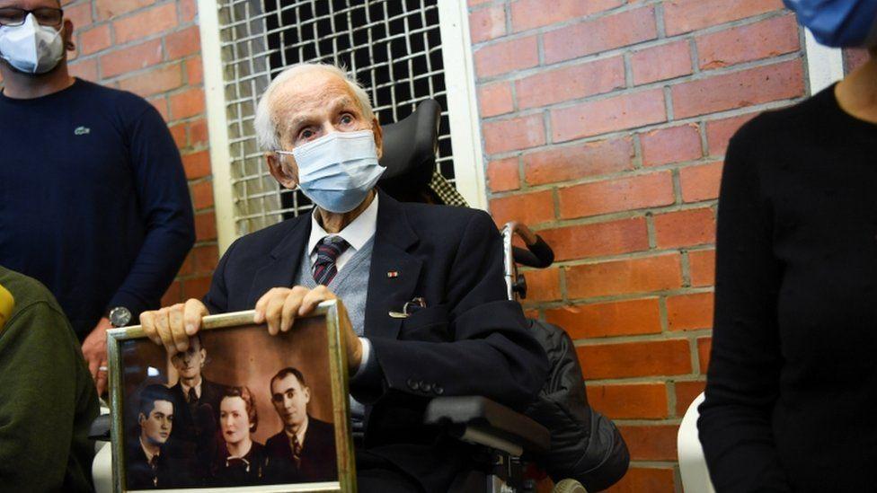 Der Holocaust-Überlebende Leon Schwarzbaum hält ein Bild im Gerichtssaal während eines Prozesses gegen einen 100-jährigen ehemaligen Wachmann des Konzentrationslagers Sachsenhausen vor dem Landgericht Neuruppin in Brandenburg, Deutschland, 7. Oktober 2021