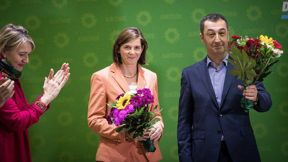 Katrin Göring-Eckardt (C) and Cem Özdemir hold flowers next to Federal chairwoman Simone Peters (L) at Green news conference in Berling (25 September)