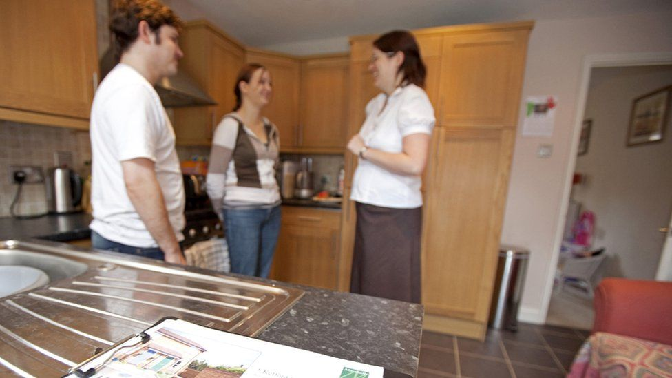 Couple being shown round a house