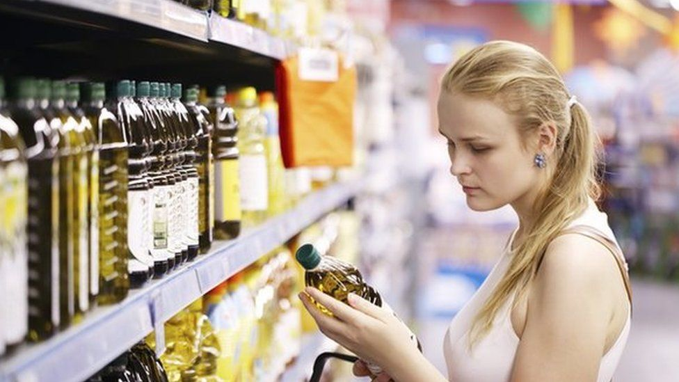 Woman checking price of cooking oil