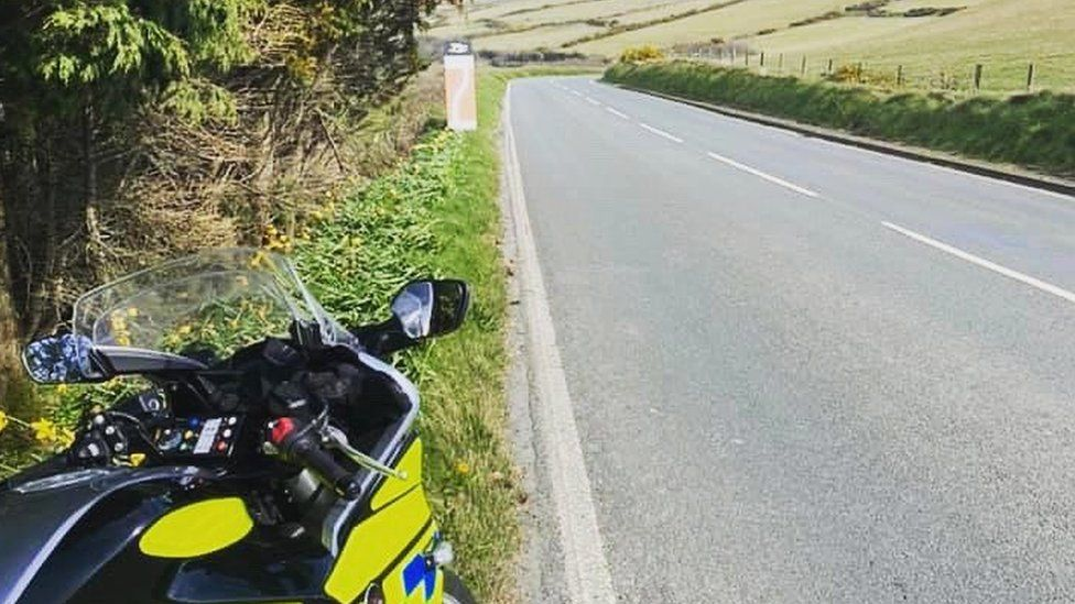 Police motorbike parked next to a clear road
