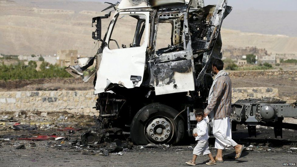 """A man and his son walk past a truck hit by a Saudi-led air strike in Yemen""""s northwestern province of Amran"""