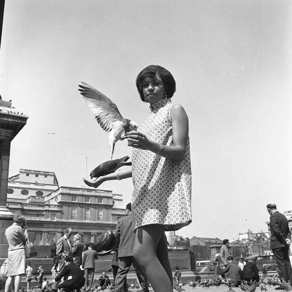 Woman outdoors holding a bird