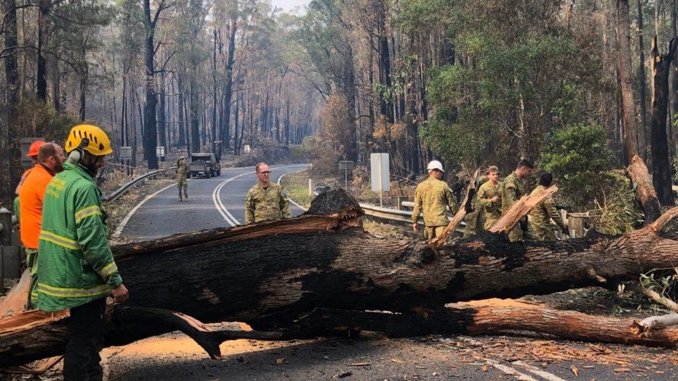 Firefighters clearing a road