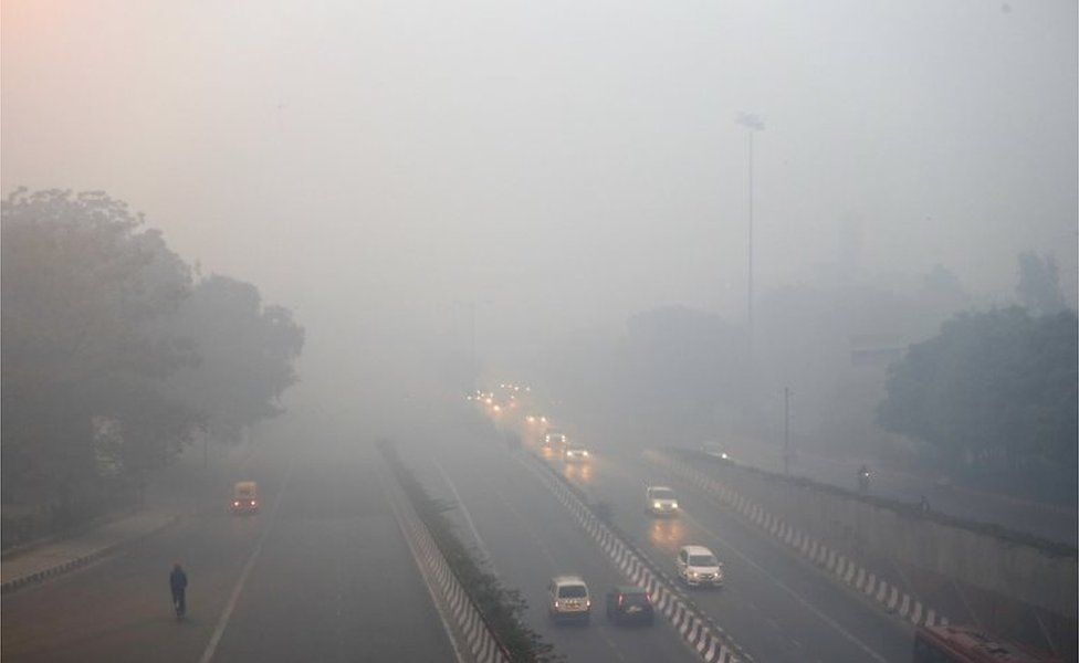 Traffic moves on a road enveloped by smoke and smog, on the morning following Diwali festival in New Delhi, India, Monday, Oct. 31, 2016.