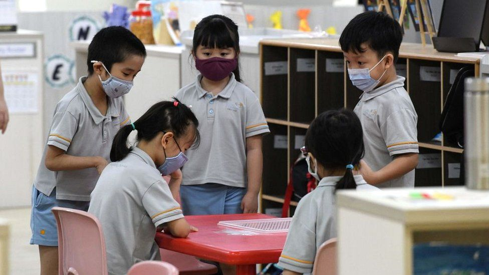 Children wearing face masks gather around a table inside their classroom in Singapore