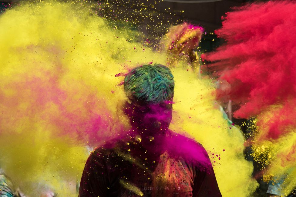 People throw coloured powder as they celebrate Holi, in Jodhpur, India, on 29 March 2021