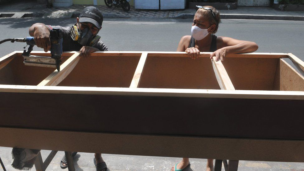 Furniture-maker and his wife working on a coffin in Guayaquil, 16 Apr 20