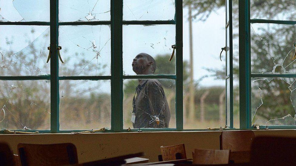 A man walks past bullet-shattered windows at Garissa University (file photo)