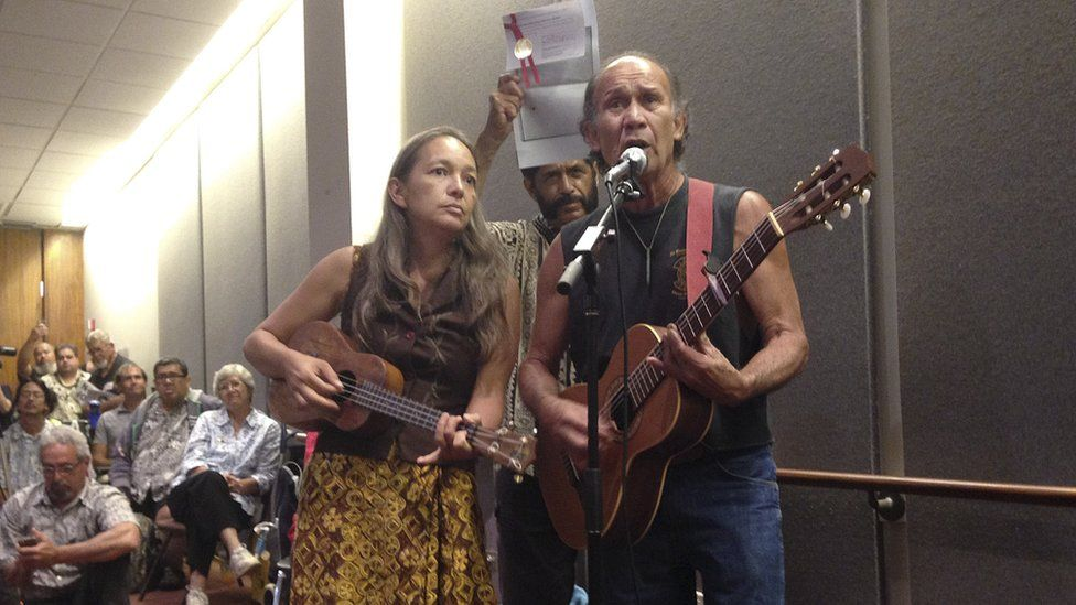 Laulani Teale, left, and Liko Martin, right, sing while Palani Vaughan, centre rear, holds up a copy of Queen Liliuokalani's protest of the overthrow of Hawaii at the Hawaii state Capitol in Honolulu on Monday, June 23, 2014.
