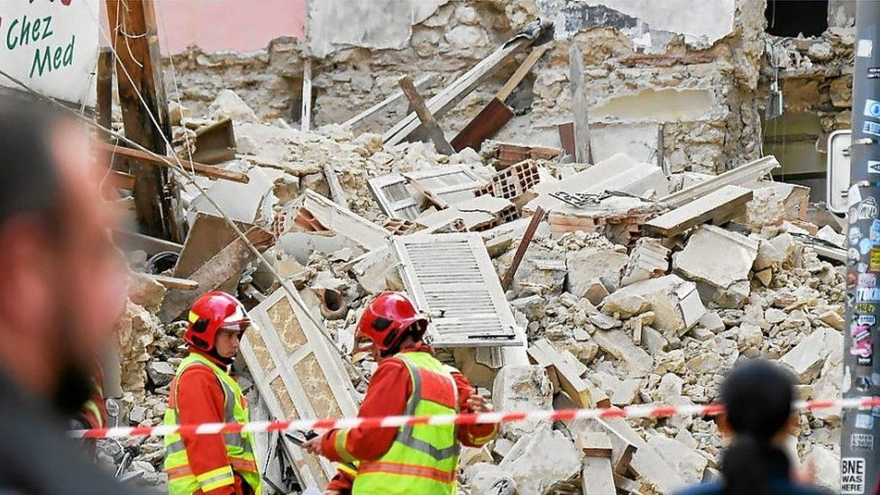 Firefighters stand afoot the rubble of the collapsed buildings in Marseille, France