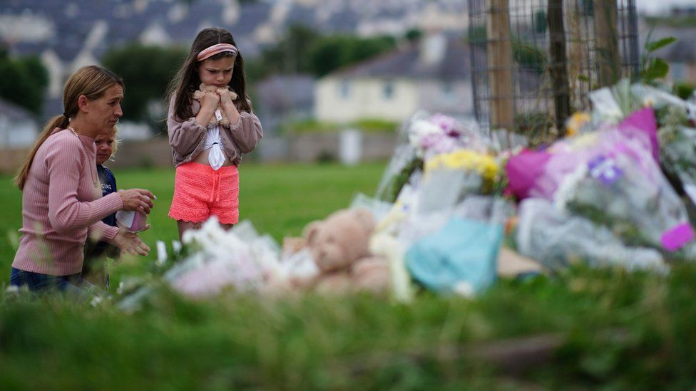 A woman and two children look at floral tributes to the five victims