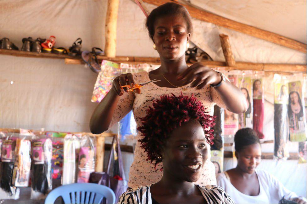 Refugee entrepreneur Penina cutting hair
