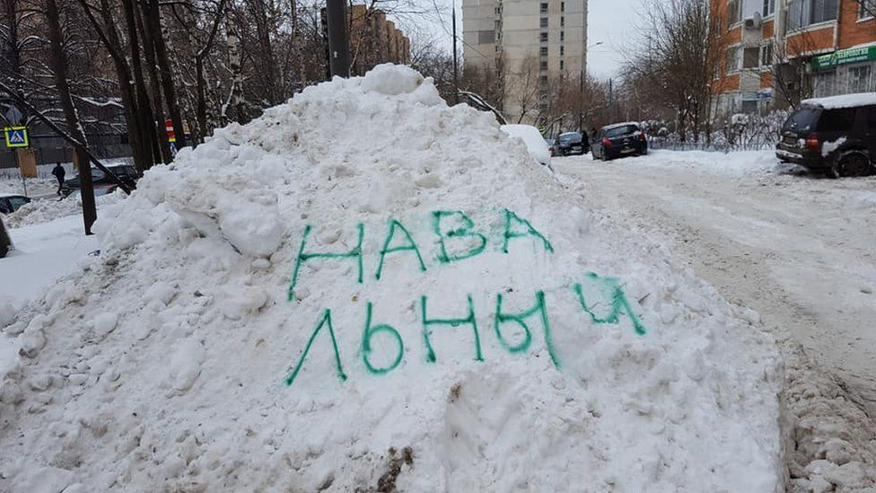 The name of Russian opposition leader Alexei Navalny spray-painted on a snow drift in Moscow.