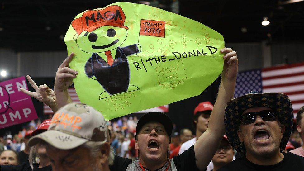 "Picture of a man holding up a sign referencing the subreddit board ""The Donald"". The QAnon conspiracy has spread to mainstream social networks such as Reddit"