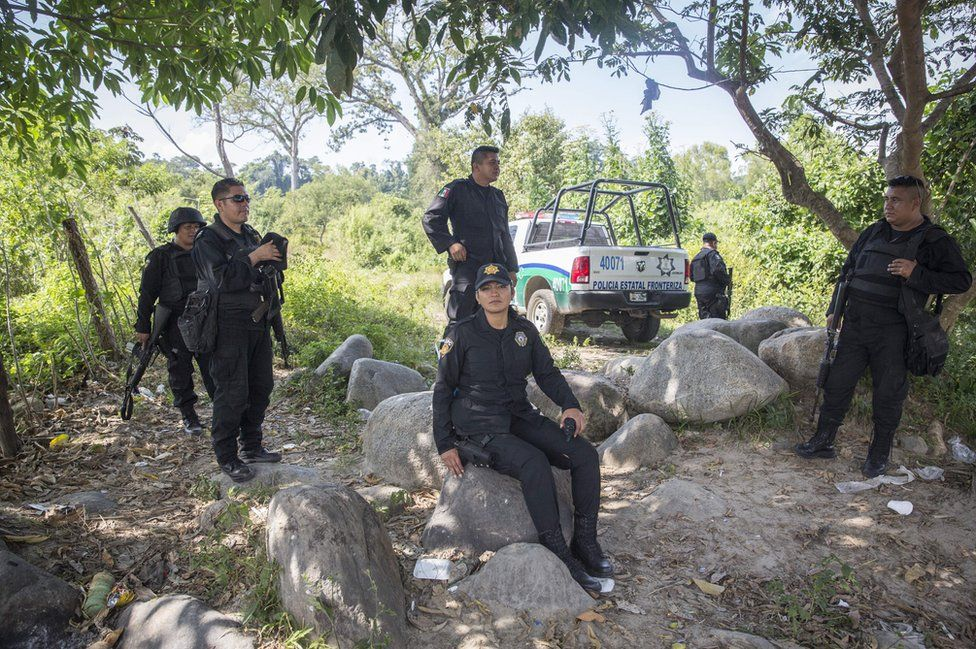 Police stand in the shade of the trees