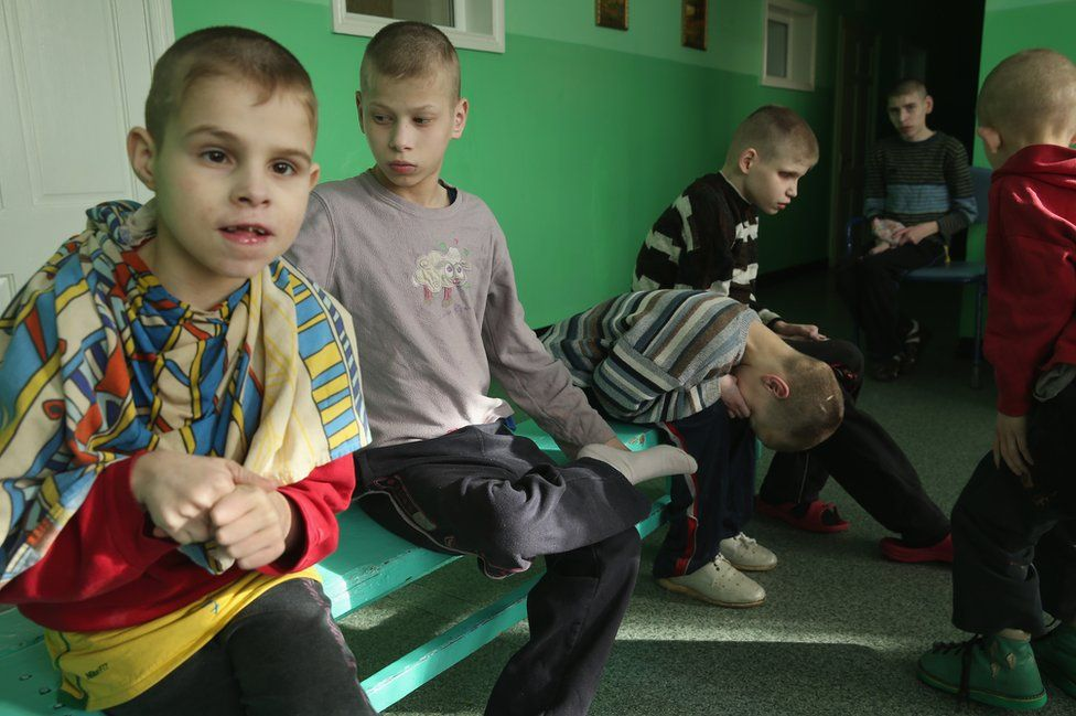 Young boys sit on a bench in their wing at the Vesnova Home for Invalid Children