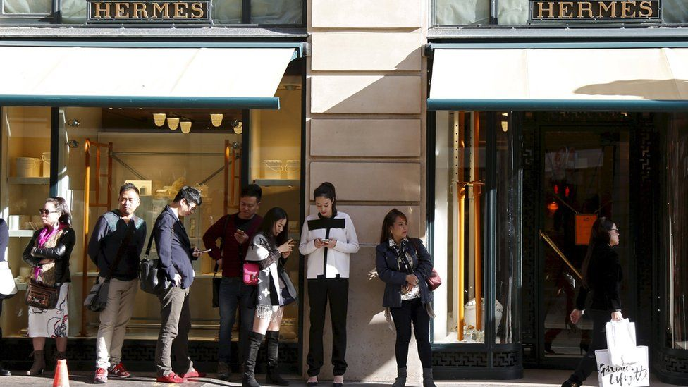 Customers queue up as they wait the opening of the main shop of French luxury group Hermes in Paris, France, in this September 23, 2015 file photo