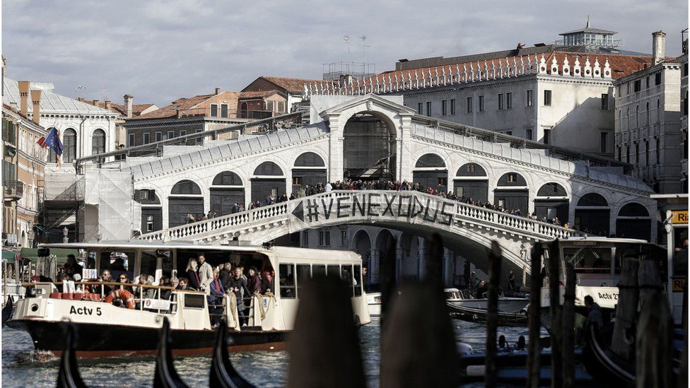 People gather on a bridge during a demonstration against the increasing number of tourists in Venice on November 12, 2016