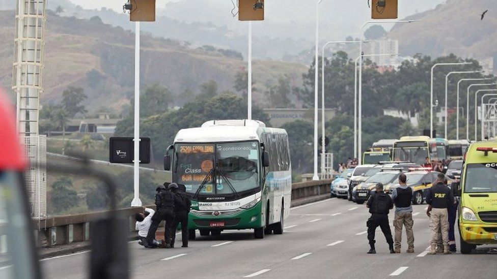 A woman faints as she gets off the bus where a man is holding passengers hostage in Rio