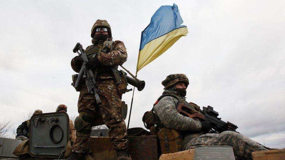 Ukrainian servicemen ride on an armoured personnel carrier at a checkpoint near the eastern Ukrainian town of Debaltseve, Donetsk region, on 24 December 2014