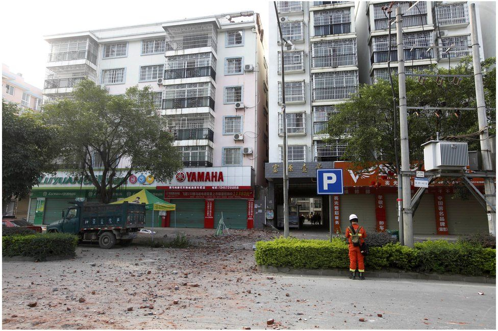 A Chinese firefighter stands at the scene of an explosion in Liucheng county in southern China's Guangxi Zhuang Autonomous Region Thursday, 1 October 2015