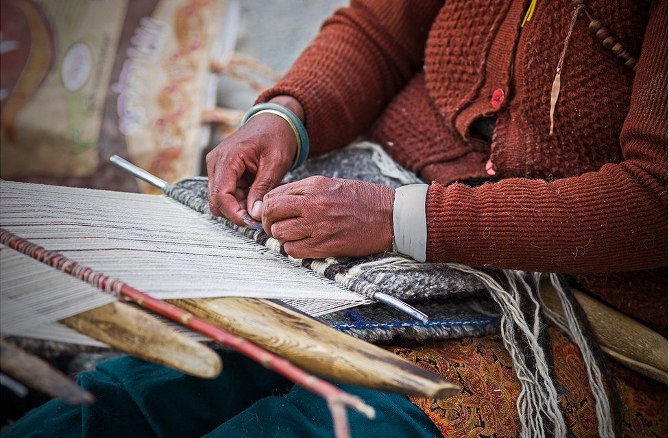 A woman weaves threads on a loom on her lap