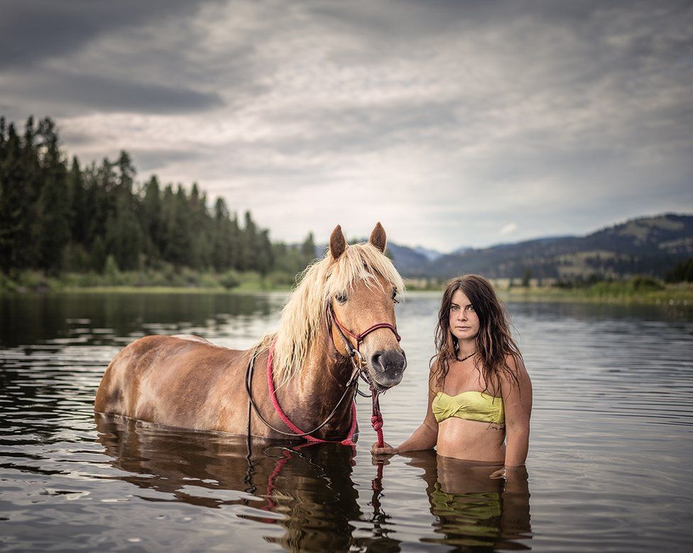 Jessica stands in water with her horse