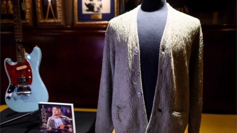 Kurt Cobain's iconic mohair green cardigan and his Fender Mustang guitar, sold at auction in New York in October 2019