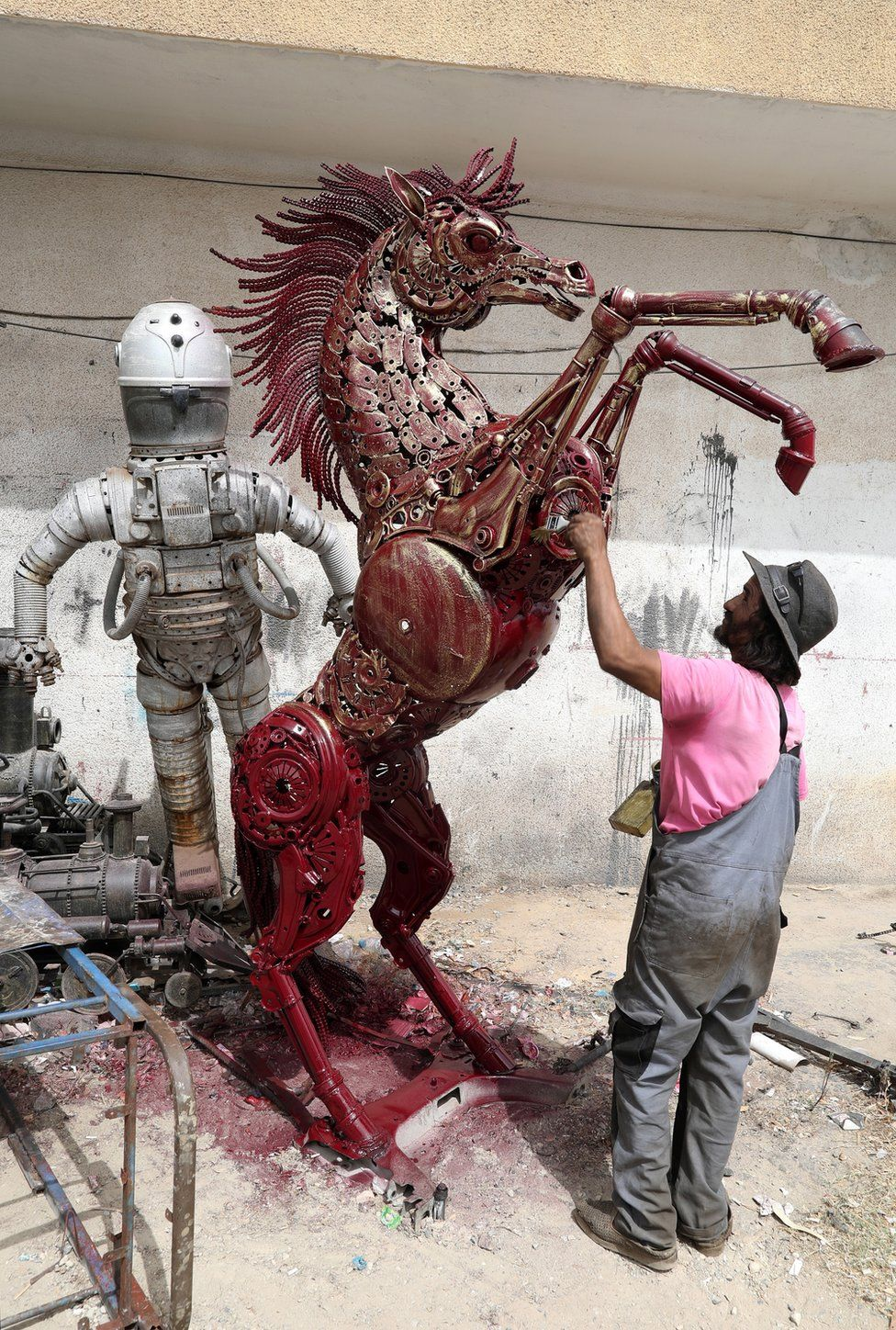 A man works on a metal sculpture of a horse.