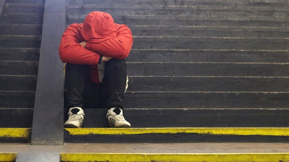 Young homeless man sitting on steps.