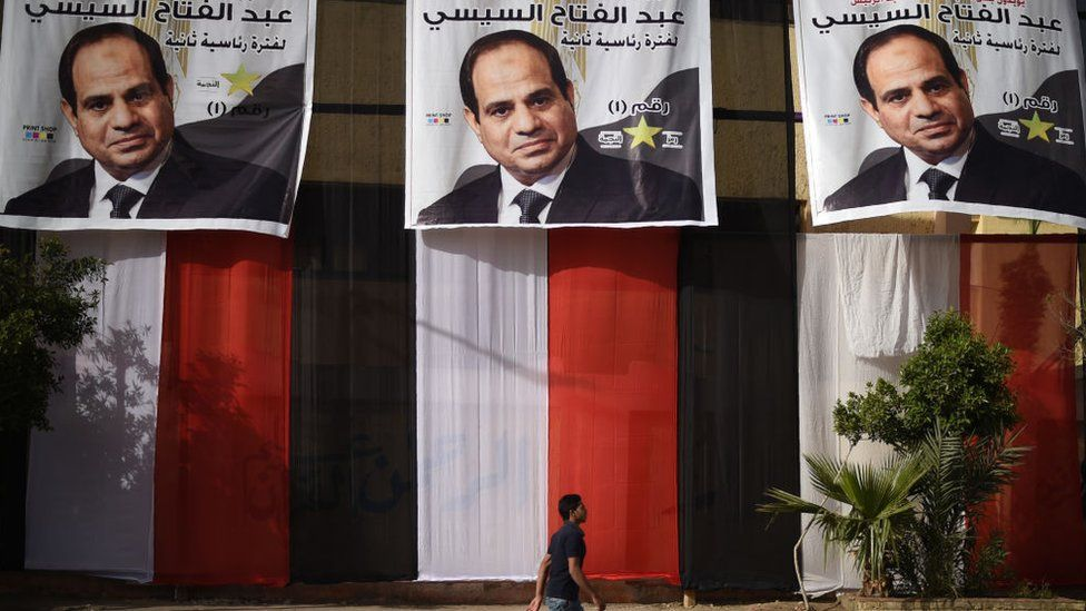 Man walks past election posters of Egyptian President Abdul Fattah al-Sisi (March, 2018)