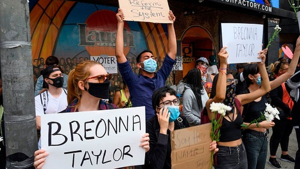 Black Lives Matter protesters hold up signs as they commemorate Breonna Taylor on what would have been her 27th birthday in Hollywood, California