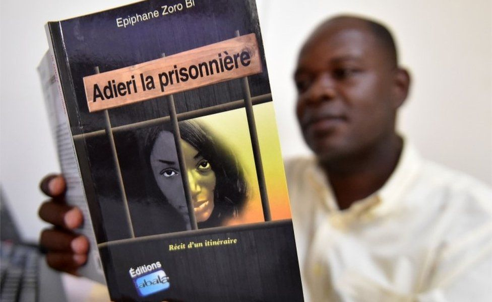 """A man reads the book """"Adieri la prisonniere"""" (Adieri the prisoner) by Ivorian writer Epiphane Zoro Bi in Abidjan on May 15, 2018. Written by Ivorian judge Epiphane Zoro Bi, this book tells the story of Ituri, a northeastern province of the DRC, where since 1999 clashes between Hemas pastors and Lendu farmers have led to the death of more than 60,000 people and have displaced 600,000"""