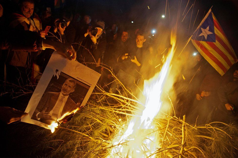 People burn images of Spain's King Felipe VI as they attend a protest against the detention of former Catalan leader Carles Puigdemont in Girona, Catalonia, north-eastern Spain, 25 March 2018.