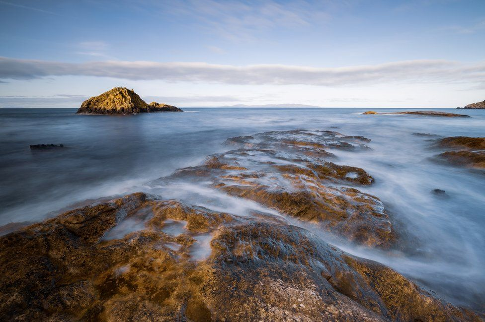 Waves lap over rocks on the beach on a clear, blue-sky day in Newcastle in County Down