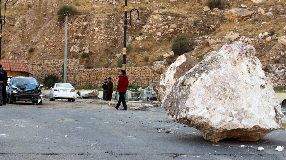 An Iraqi Kurdish man walks by a large rock which fell from the top of a mountain during the earthquake that hit Darbandikhan town