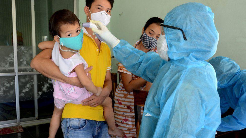 A family have their temperatures taken in Da Nang, Vietnam