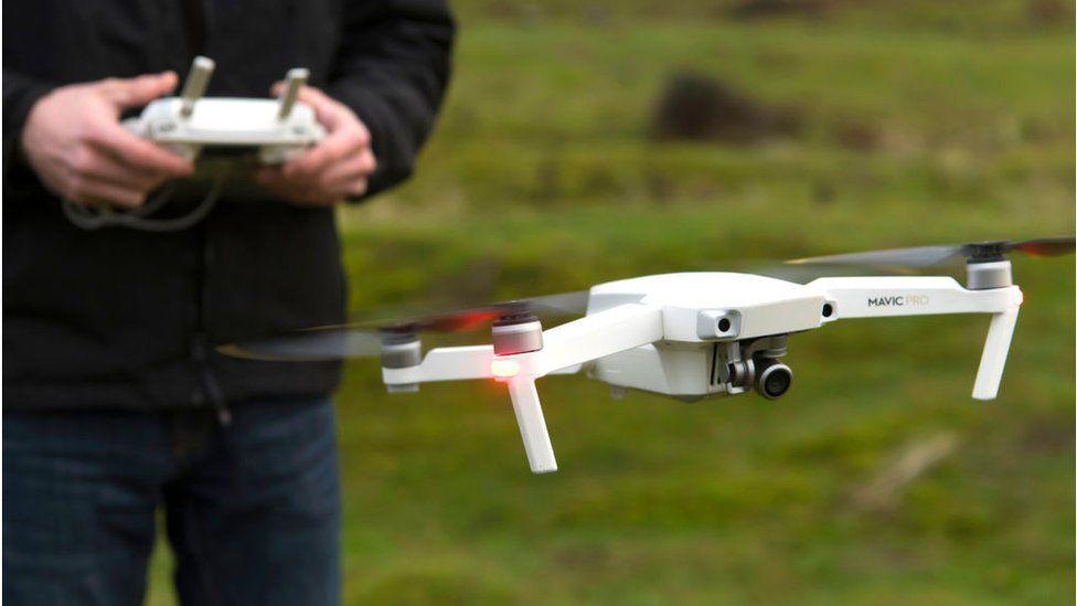 A drone pilot flying a DJI Mavic Pro in Wales
