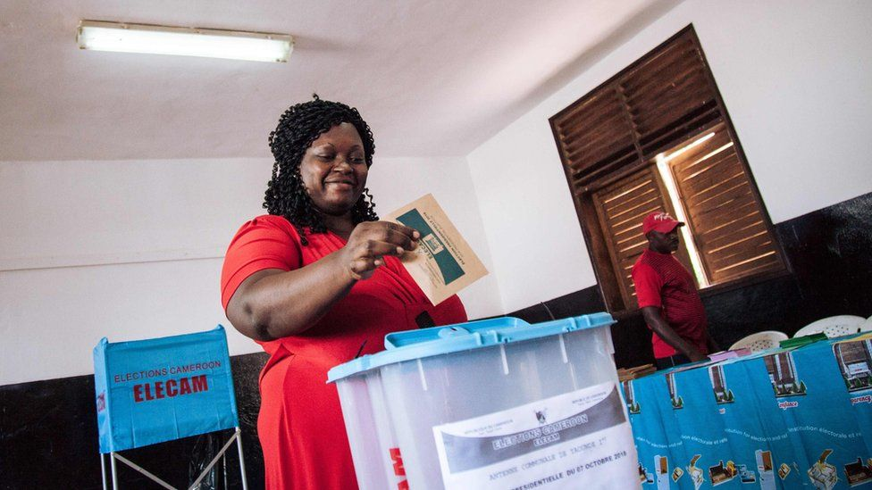 A woman casts her ballot in the polling station where the incumbent President is expected to vote in Bastos neighbourhood in the capital Yaounde