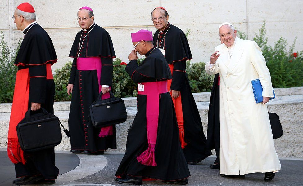 Pope Francis, flanked by Archbishop of Bombay Cardinal Oswald Gracias (L) and other bishops, arrives at Synod Hall in Vatican City on 24 October 2015