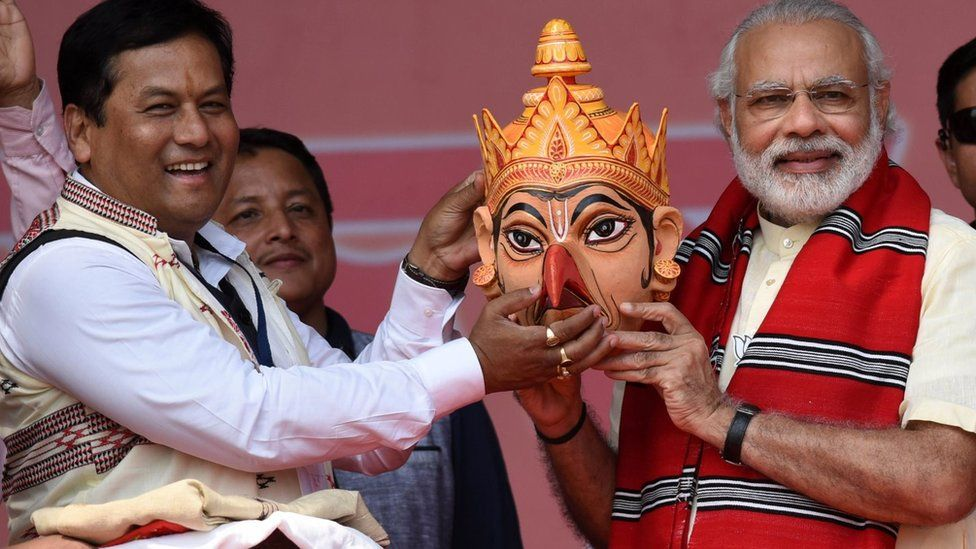 India's Prime Minister Narendra Modi(R) poses with Bharatiya Janata Party (BJP) election candidate Sarbananda Sonwal as he is given a traditional Assamese mask at an election rally at Majuli Island on March 26, 2016,