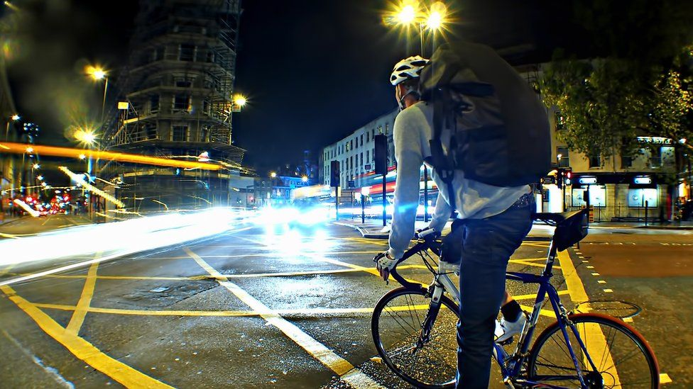 man on a bike in the city at night