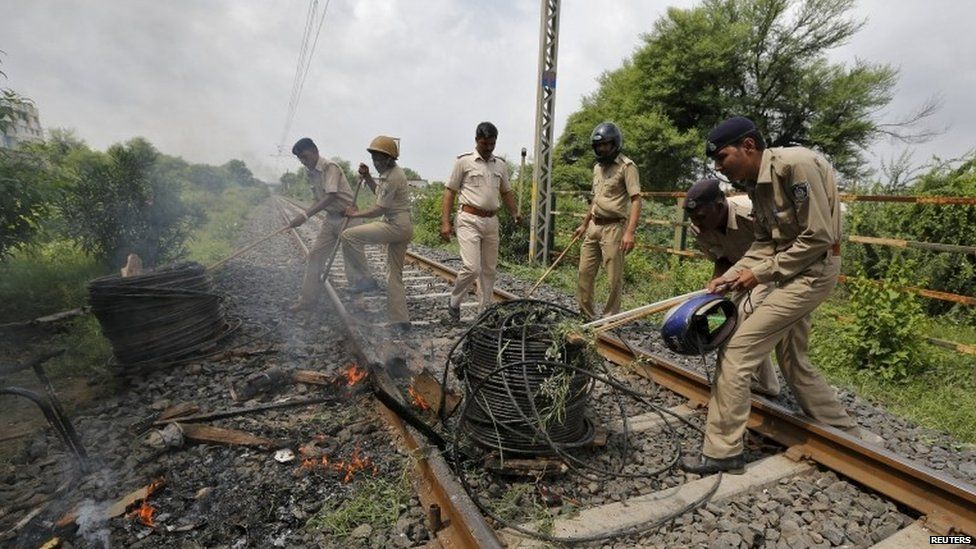 Policemen remove cables from a railway track which were set on fire by the protesters in Ahmedabad, India, August 26, 2015.