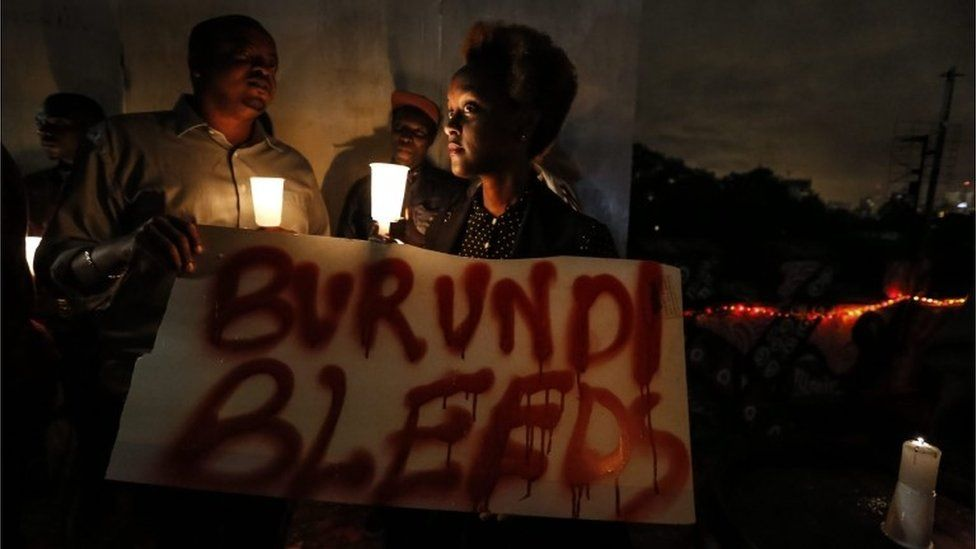 "A Burundian expatriate woman holds a placard reading ""Burundi bleeds"" during a candlelight vigil held for Burundi in Nairobi, Kenya, 13 December 2015"
