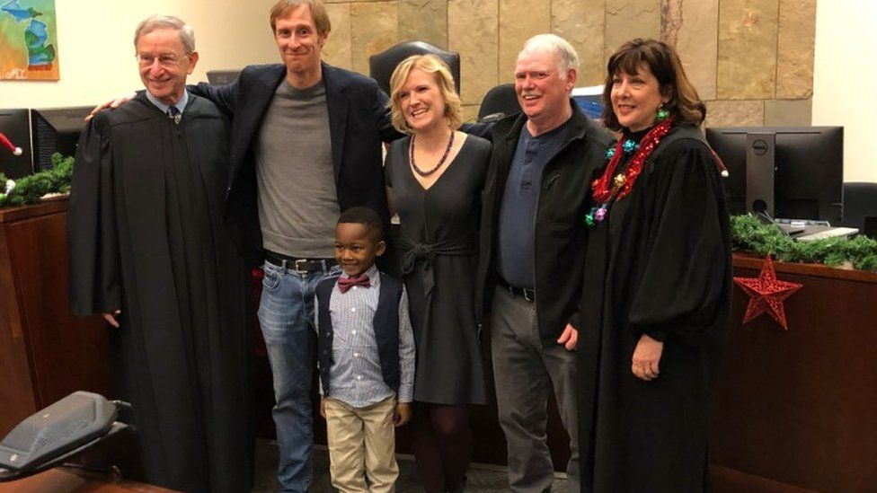 A picture shared by Kent County, Michigan's Facebook page shows a little boy named Michael being formally adopted in court